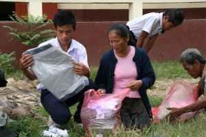 Foreldrene hjelper barna å se over at de klærne de har fått, passer.