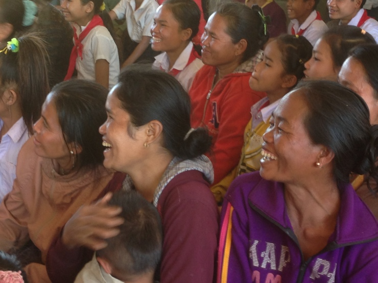Glade foreldre under utdeling av skolepakker.