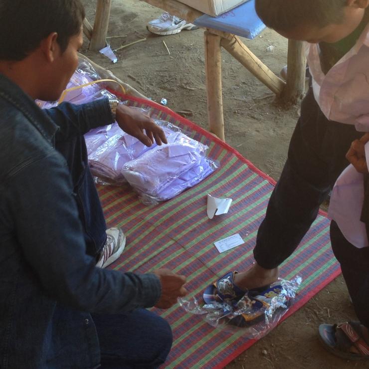 Satad hjelper en liten gutt å bytte sko