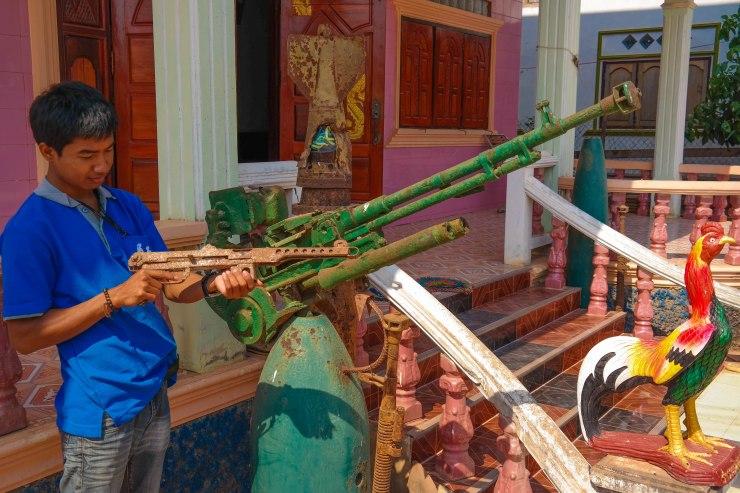 Somchai utenfor gjestehuset med litt dekorative våpen fra Vietnamkrigen